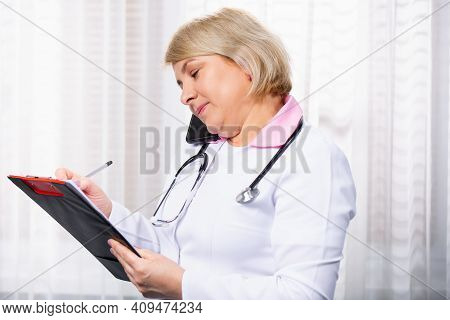 Caucasian Doctor Handsome Woman With Stethoscope Talking On Mobile Phone, Smartphone Calls At Clinic