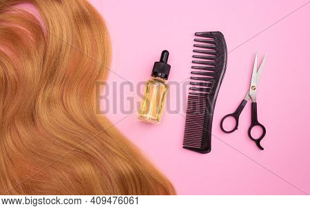 Brown Artificial Hair On A Pink Background, Cosmetic Oil In A Glass Bottle With An Eyedropper, Comb