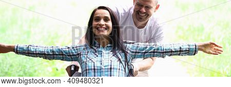 Cheerful Partner Roll Happy Beautiful Woman In Wheelchair. Unequal Love Between Man And Paralyzed Wo