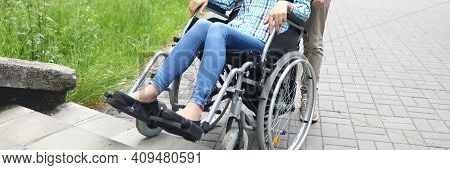 Man Lift Disabled Person With Stroller Up Stairs In City. Couple Walk. Disabled Person. Paralyzed Wo