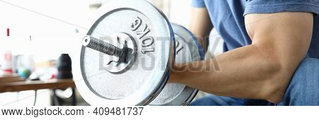 Large Male Hand With Biceps Hold Ten Kilogram Metal Dumbbell. Man Sit On Simulator And Pumps Muscles