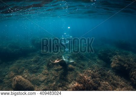 Free Diver Making Ring Bubbles In Sea. Sporty Man Freediver In Summer Sea