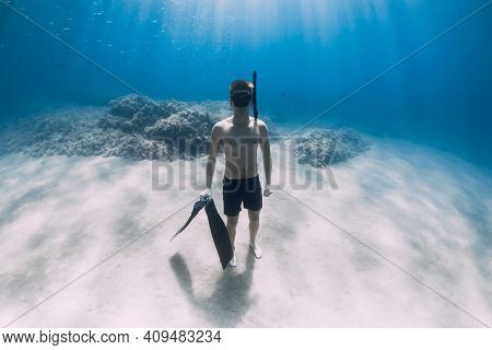 Sporty Man Freediver Stay With Fins On Sandy Bottom Underwater In Tropical Sea.