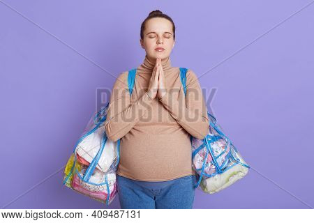 Beautiful Pregnant Concentrated Woman In Casual Attire With Big Baby Bump Isolated Over Lilac Backgr