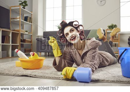 Housewife In Curlers And Skin Care Face Mask Cleaning Floor With Detergent And Daydreaming