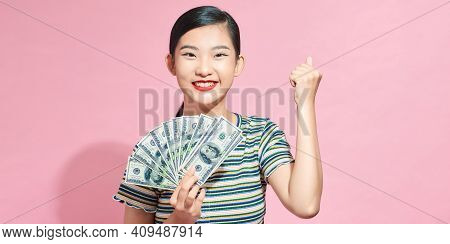 Happy Young Woman Doing Winner Gesture, Holding Fan Of Cash Money In Dollar Banknotes Isolated On Pi
