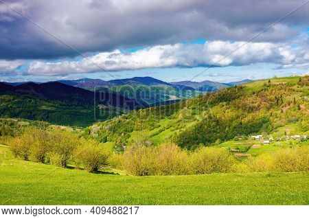 Rural Fields On Rolling Hills In Springtime. Borzhava Mountain Ridge In The Distance. Carpathian Lan