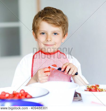 Little Blond Kid Boy Helping And Making Strawberry Jam In Summer. Funny Child Cleaning Berries And P