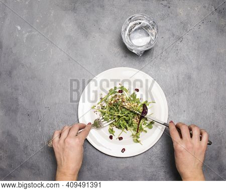 Woman Eating Fresh Green Sprouts Microgreens And Seeds In White Plate On Grey Background With Silver