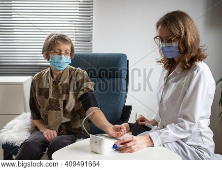 doctor consulting elderly female patient at home dog in foreground