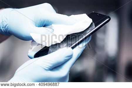 Coronavirus COVID-19 sanitize cleaning disinfection of smartphone.Office sanitizing wipe wiping phone with disinfecting wipes.