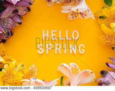 Text Hello Spring On Bright Yellow Background With Border Of Fresh Alstroemeria Flowers. Seasons Gre