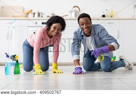 Happy African American Couple In Colorful Gloves Cleaning Floor Together In Kitchen, Using Cloth And