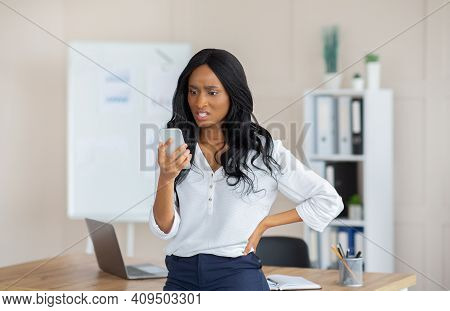 Annoyed Black Business Woman Looking At Her Smartphone, Irritated About Upsetting News At Office. Un
