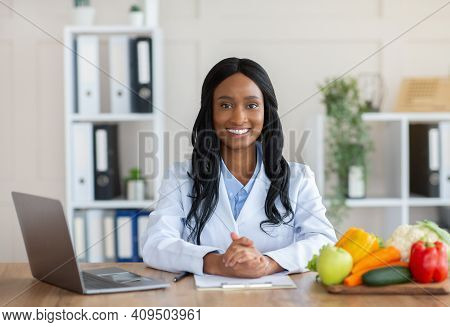 Smart Eating And Healthy Nutrition Concept. Portrait Of Positive Black Dietitian Looking At Camera A
