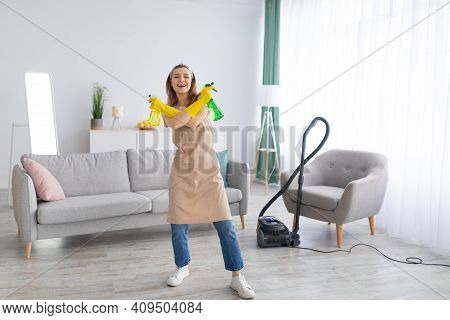 Cheerful Young Housemaid Holding Detergent Spray Bottles Like Guns At Clean Home, Free Space. Positi