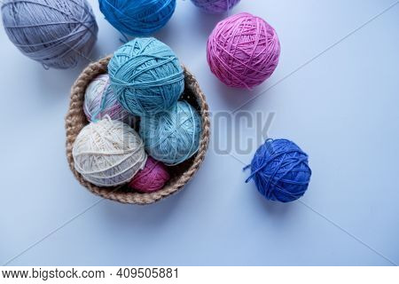Yarn In A Knitted Basket On A White Background. Yarn Of Different Colors. The Concept Of Creating A