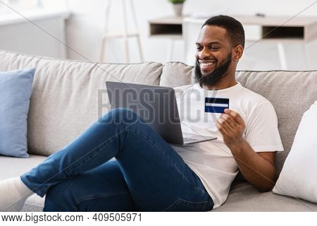 African Guy Holding Credit Card Shopping Online Via Laptop Computer Sitting On Couch At Home. Happy