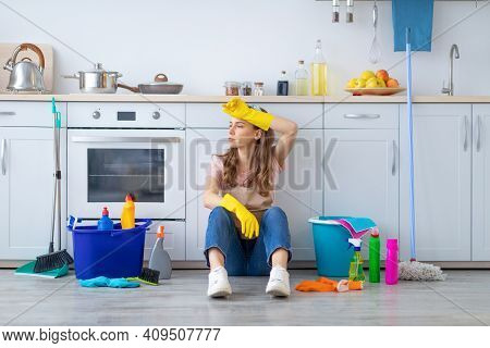Young Housewife Tired From Domestic Work Sitting On Kitchen Floor, Wiping Her Forehead. Overworked M