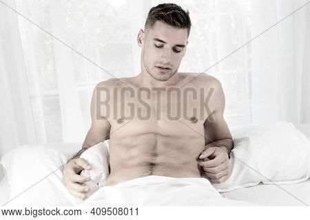 Handsome Naked Muscular Man With Stubble, Sixpack Abs Lying In Bed Covered With Sheet