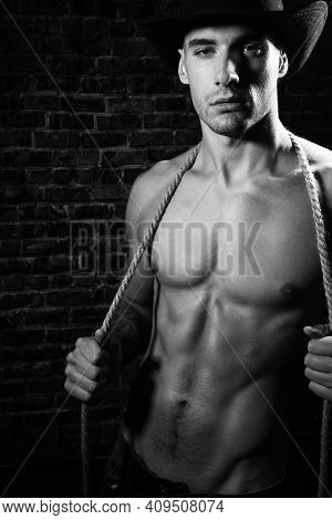 Portrait Of Handsome Shirtless Cowboy Looking At Camera Wearing Hat With Defined Pecs And Sixpack Ab