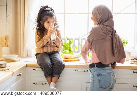 Cute Little Arab Girl And Her Muslim Mom In Hijab Spending Time Together In Kitchen, Small Female Ki