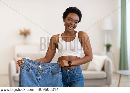 Weight Loss Motivation. Fit African American Lady Holding Large Jeans After Successful Slimming Posi