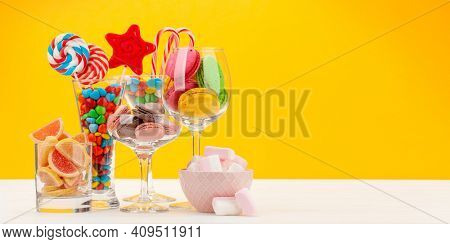 Various sweets assortment. Candy, bonbon, chocolate and macaroons in cocktail glasses over yellow background. With copy space