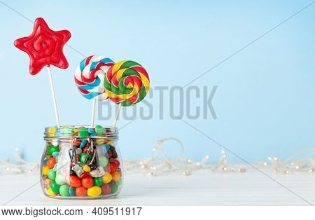 Various sweets assortment. Candy, bonbon, lollipop in glass can over blue background. With copy space