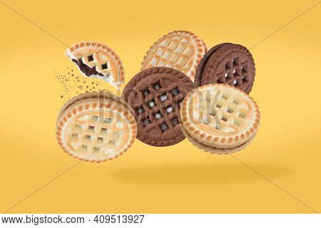 Flying Cookies Isolated On Yellow Background. Sandwich Cookies, Chocolate. Cookies In Tha Air