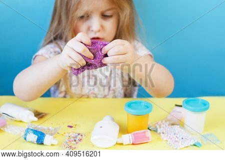 Blonde Girl Hold Purple Slime Isolated On Blue Background. Child Playing With Slime Toy. Making Slim