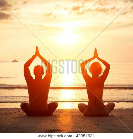 Yoga practice, young couple sitting on the beach of the sea in the lotus position at sunset.