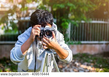 Selective Focus To Boy Taking A Picture With Film Camera And Tripod. Vintage Camera.