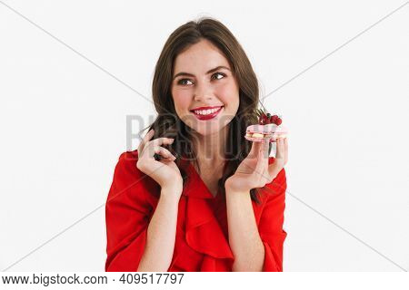 Beautiful lovely young woman in red dress tempted to eat a tasty cake isolated over white background