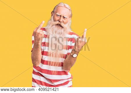 Old senior man with grey hair and long beard wearing striped tshirt showing middle finger doing fuck you bad expression, provocation and rude attitude. screaming excited