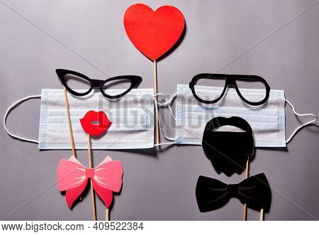 Two Medical Masks With Glasses, Lips And Moustaches With A Red Heart Above Them On A Gray Background
