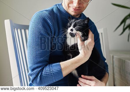 Young Man Holding His Cat In Arms During Sunny Day. Themes Trust, Care And Friendship Between People