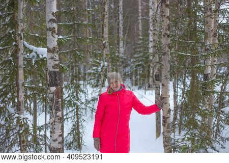 Woman In A Bright Pink Warm Jacket In A Winter Snowy Forest. Winter Nature Of The North Of Russia. S