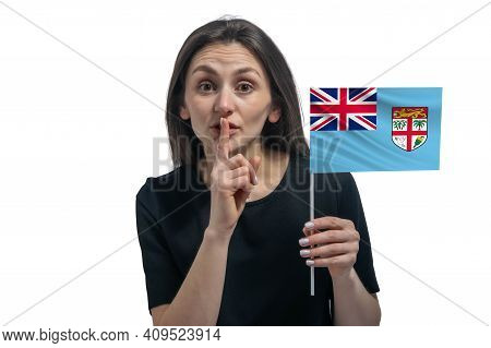 Happy Young White Woman Holding Flag Of Fiji And Holds A Finger To Her Lips Isolated On A White Back