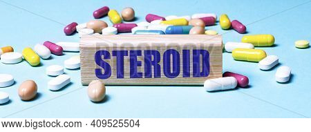 A Wooden Block With The Word Steroid Stands On A Blue Background Among Multi-colored Pills. Medical