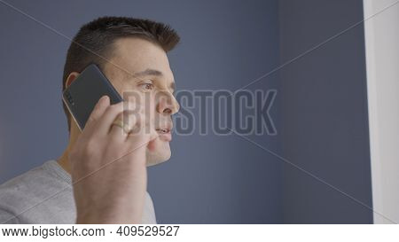 Man Is Talking To Friend On Phone At Home. Action. Man Is Having Normal Friendly Conversation On Pho