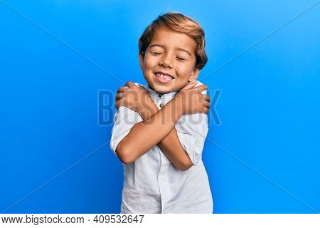 Adorable latin kid wearing casual clothes hugging oneself happy and positive, smiling confident. self love and self care