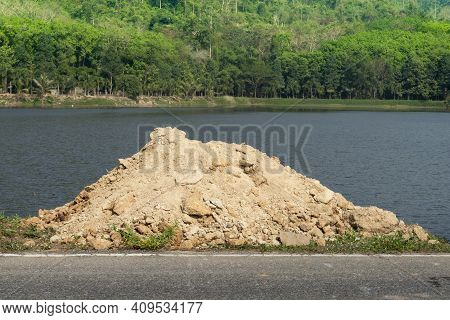Pile Of Soil Beside The Asphalt Road. Have A Skin Color Like Laterite Soil. With Nature Of River And