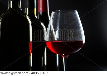 Several Different Bottles Of Wine And A Glass With Red Wine On A Dark Glossy Background.