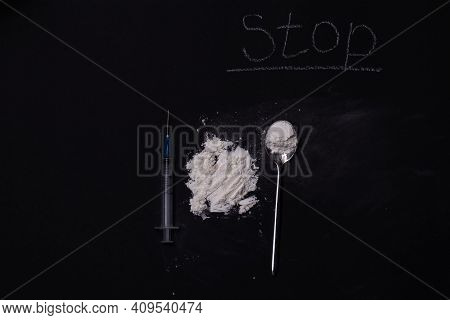 Heroin And Drug Paraphernalia Are Placed On A Black Background. The Concept Of Crime And Drug Addict