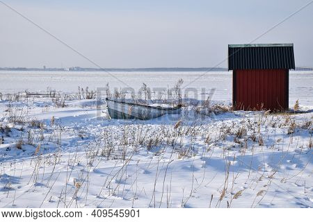 Old Rowing Boat By A Red Fishing Cabin In Winter Season