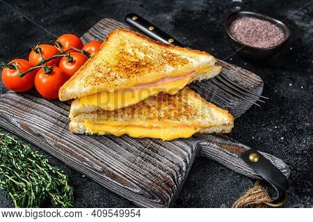 Grilled Ham And Cheese Sandwich On A Cutting Board. Black Background. Top View
