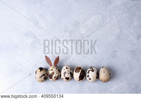 Quail Egg In The Form Of An Easter Bunny In A Row With Quail Eggs On A Light Gray Background, Minima