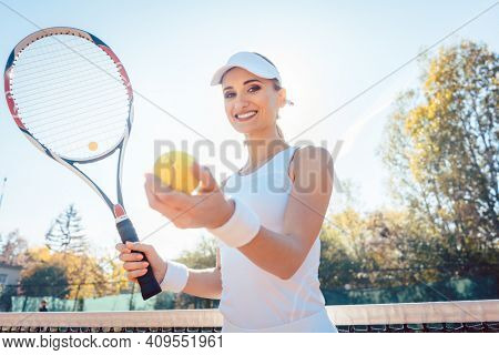 Beautiful woman in white attire getting ready to play tennis