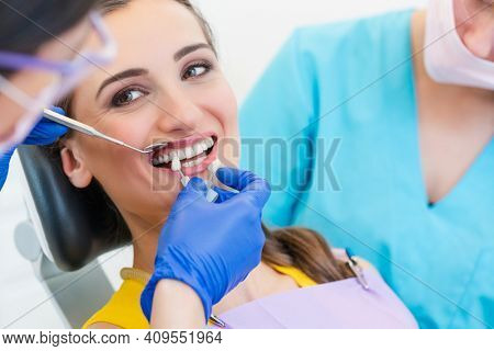 Woman discussing dental bleaching with her dentist with sample chart